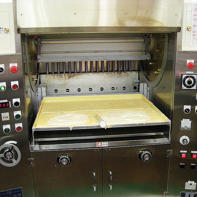 左右にたくさんのボタンがついた、この機械でバウムクーヘンを作ります。